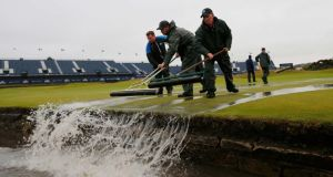 Groundstaff remove water from the first green after torrential rain forced play to be suspended. Photograph: Paul Childs/Reuters