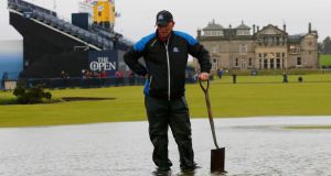 A member of the groundstaff stands in a puddle on the first fairway after torrential rain caused play to be suspended during the second round of the British Open. Photograph: Paul Childs/Reuters