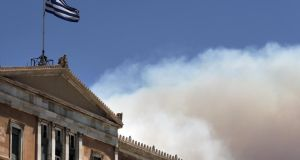 A Greek national flag flutters atop the parliament building as smoke from  wildfire rises in Athens, Greece, July 17th, 2015. Photograph: Alkis Konstantinidis/Reuters