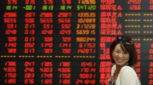 An investor smiles as she walks past an electronic board showing stock information at a brokerage house in Fuyang,  China, yesterday. Photograph: Reuters
