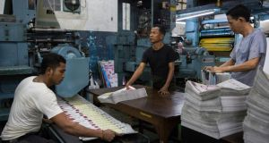 Staff oversee the printing of a Burmese-language newspaper in Rangoon (Yangon).  Photograph: Adam Dean/New York Times