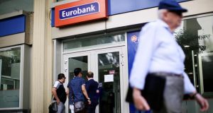 Customer wait to enter a Eurobank Ergasias SA branch in Athens. Photograph: Matthew Lloyd/Bloomberg