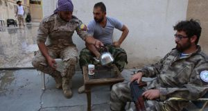 Members of the Assyrian Gozarto Protection Forces, consisting of Sutoro militia, a pro-Syrian government Syriac Christian movement, and other Assyrian fighters rest and drink tea before heading to  the front line in the battle against  Islamic State in the northeastern Syrian province of Hasakeh on July 13th. Photograph: Youssef Karwashan/AFP/Getty Images
