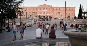 People sit outside the Greek parliament in Athens.  Standard & Poor's rating raised Greece's credit rating by two notches to CCC+ after the indebted country reached a preliminary deal with its creditos for a third bailout deal. Photograph: AFP  Photo
