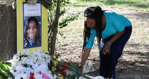 A woman places a bouquet of roses at a memorial for Sandra Bland near Prairie View A&M University on Tuesday. Photograph: Pat Sullivan/AP