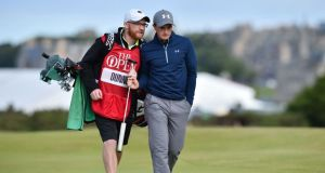 Paul Dunne talks to his caddie Alan Murray as they walk up the 16th fairway. Photograph: AFP Photo