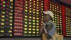 Troubling times: checking stock prices recently in Nanjing, China. Photograph: Reuters/China Daily