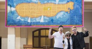 The Edge, Yoko Ono and Bono stand infront of a tapestry in memory of John Lennon at Ellis Island. Photograph: Edu Bayer