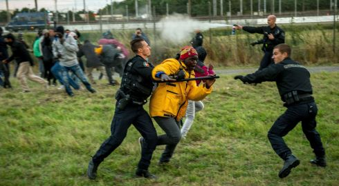 French gendarmes try to stop migrants on the Eurotunnel site in Coquelles near Calais. Photograph: AFP/Getty Images