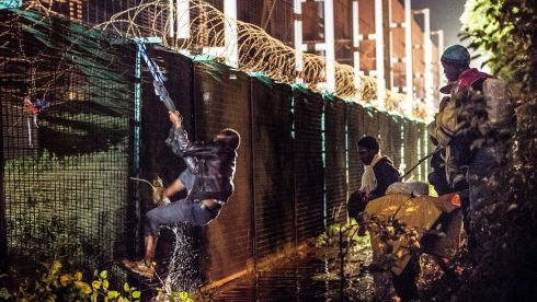 A migrant climbs a security fence of a Eurotunnel terminal in Coquelles near Calais, northern France. Photograph: AFP.