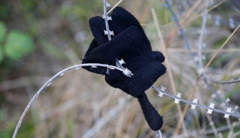 A glove left by a migrant is seen on razor-wire near train tracks which lead to the Channel Tunnel in Frethun, near Calais. Photograph:Pascal Rossignol/Reuters.