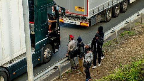 Migrants speak with a truck driver as they walk alongside vehicles on the route leading to the Eurotunnel in Coquelles. Photograph: AFP/Getty Images