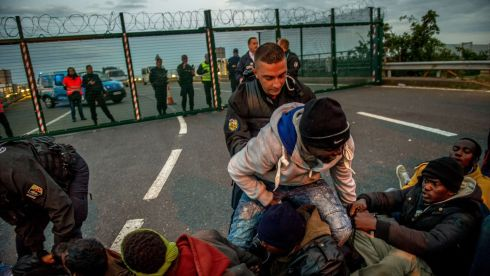 French gendarmes try to separate migrants on the Eurotunnel site near the boarding docks in Coquelles near Calais in northern France. Photograph: AFP/Getty Images