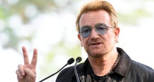 Bono holds up a peace sign at the unveiling of a giant tapestry in honour of John Lennon on Ellis Island. Photograph: AFP/Getty Images