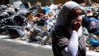 A Lebanese woman covers her nose from the smell as she walks on a street partly blocked by piles of garbage in Beirut. Photograph: Hassan Ammar/AP
