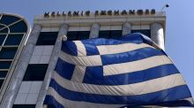 A Greek flag is pictured outside the Athens Stock Exchange in Athens Photograph:  Aris Messinis/AFP/Getty Images