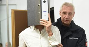One of the two defendants, identified only as Ayoub B, covers his face with a file folder as he is led into a courtroom in Celle, Germany, on Sunday. Photograph: Holger Hollemann/EPA.