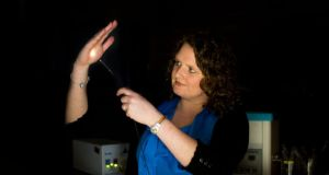 Dr Sinéad O'Keeffe of the University of Limerick demonstrating simulated light emission from the radiotherapy sensor. Photograph:   Sean Curtin
