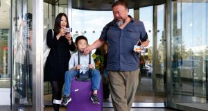 Chinese artist Ai Weiwei his  son Ai Lao at Munich airport: the activist has said  that his homeland must become a democratic society. Photograph: Matthias Schrader/AP