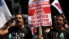 "Protesters from the Communist-affiliated trade union PAME at an anti-austerity demonstration  in Athens on Wednesday.  The parliamentary spokesman for the  Syriza party urged it  to unite behind a new funding agreement, saying the country wanted a full bailout immediately rather than a bridge loan. The placard reads,  ""No to layoffs. Steady and permanent jobs for everybody"". Photograph:  REUTERS/Yiannis Kourtoglou"