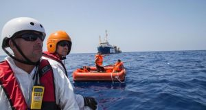 Rescued migrants (in orange inflatible boat) located about 110km northwest of Libyan capital, Tripoli, on August 5th, 2015.  Photograph: Marta Soszynska/MSF