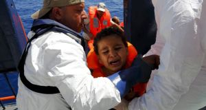 A child migrant  is brought aboard the Migrant Offshore Aid Station (MOAS) ship MV Phoenix after being rescued from an overloaded wooden boat 16km off the coast of Libya, August 6th, 2015. Photograph: Darrin Zammit Lupi/Reuters