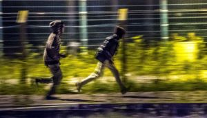 Migrants that have passed a first fence look for another passage to access the Eurotunnel terminal near Calais, northern France. Photograph: Philippe Huguen/AFP/Getty Images
