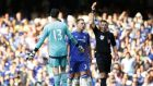 Michael Oliver shows Chelsea goalkeeper Thibaut Courtois a red card after he brought down Swansea striker Bafatimbi Gomis. Photograph: Afp