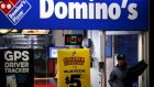 A worker carries a pizza for delivery at a Domino's pizza store in Sydney:   Fast food  companies are making healthy profits and boldly innovating in the unlikely market of Australia. Photograph: REUTERS/David Gray