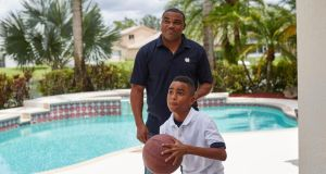 Shawn Wooden, a former Miami Dolphins player and important advocate of the concussion settlement with the NFL, with his son, Shane, at home in Pembroke Pines. Photograph: Ryan Stone/The New York Times