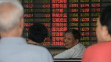Investors chat in front of an electronic board showing stock information at a brokerage house in Shanghai