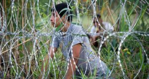 A migrant looks from behind the fence at the border from Serbia into Hungary on Saturday. The  Hungarian authorities said a record number of migrants crossed the border from Serbia last week. Photograph: Getty