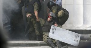An injured national guard officer is carried away  outside the parliament building in Kiev, Ukraine,  on Monday after one soldier was killed and scores injured following an explosion during clashes.   Photograph: Valentyn Ogirenko/Reuters