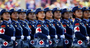 Military nurses look from atop a truck towards the Chinese president. Photograph: Damir Sagolj/Reuters