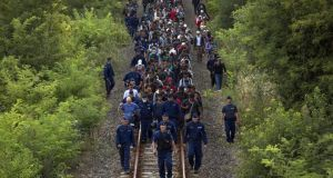 Hundreds of migrants guarded by police walk several miles along rail tracks towards the town of Szeged after breaking away from a collection point close to the Serbian border on September 8th, 2015 in Morahalom, Hungary. Photograph: Dan Kitwood/Getty Images
