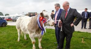 Minister for Foreign Affairs Charlie Flanagan with Christy Doherty of FBD and the first prize Belgian Blue Heifer at the Tullamore Show at the official launch of the National Ploughing Championships in Ratheniska, Co Laois. Photograph: Jeff Harvey