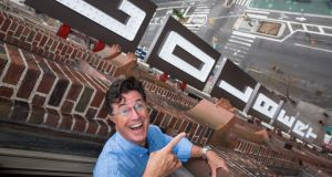 Steven Colbert points to the new sign bearing his name on the Ed Sullivan Theater in New York where his  show takes places. Photograph: Damon Winter/The New York Times