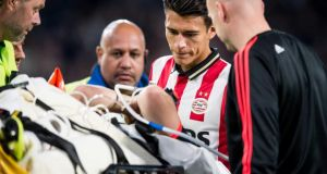 PSV Eindhoven player Hector Moreno looks on at Manchester United's Luke Shaw who is stretchered off injured following his tackle. Photograph: EPA