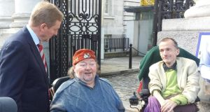 Taoiseach Enda Kenny speaking to disability activist Martin Naughton and protester Donal Toolan outside Government Buildings. Photograph: Rachel Flaherty