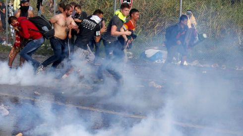 Men run from tear gas fired by Hungarian riot police at the border crossing with Serbia near Roszke, Hungary. Photograph: Marko Djurica/Reuters