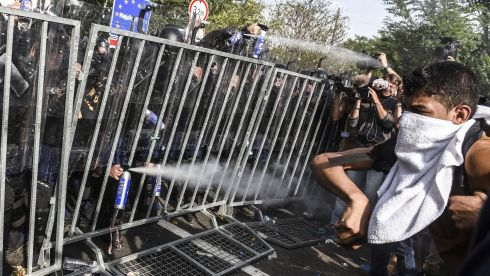 Hungarian riot police use pepper spray at the Hungarian border with Serbia near  Horgos. Photograph: Armend  Nimanjarmend Nimani/AFP/Getty Images