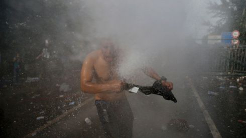 A man is hit by a jet from a water cannon used by Hungarian riot police  at a border crossing, near Roszke, Hungary. Photograph: Marko Djurica/Reuters
