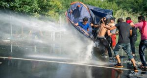 Hungarian police use water cannons against demonstratring migrants and refugees at the border crossing into Hungary, near Horgos. Photograph: Tamas Soki/EPA