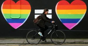 A woman cycles past a marriage equality mural in the Liberties area of Dublin. File photograph: Brian Lawless/PA Wire