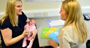 Lisa Dunne, from Swords, in Dublin, and her eight-day-old baby Sadie, with Fiona Pyne, public health nurse, receives the HSE book, 'Caring for your Baby'. Photograph: Dara Mac Dónaill