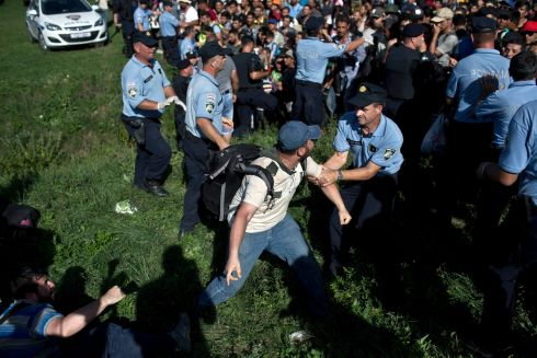 A Croatian police officer tries to stop a man from pushing through a police cordon in Tovarnik, Croatia, on Thursday. Photograph:  Marko Drobnjakovic/AP Photo