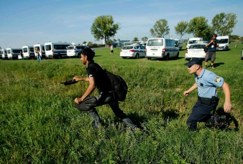 A police officer chases a man as hundreds of migrants rushed to get on buses at Tovarnik, Croatia, on Thursday. Photograph:  Antonio Bronic/Reuters