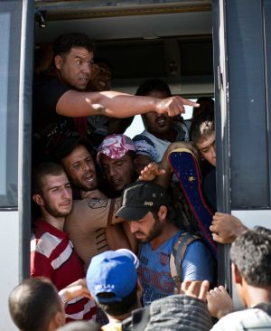 People crowd a bus provided by the Croatian government, after pushing through police lines in Tovarnik, Croatia. Photograph: AP Photo/Marko Drobnjakovic