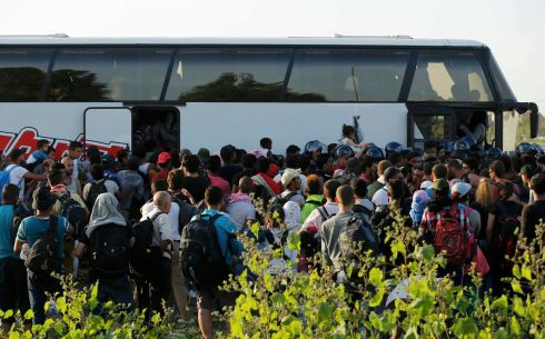 Migrants board a bus at Tovarnik rail station, Croatia, on Thursday.  Photograph: Antonio Bronic/Reuters