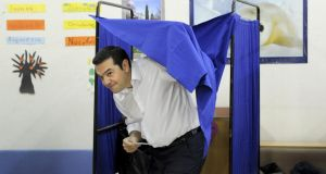 Former Greek prime minister and leader of leftist Syriza party Alexis Tsipras holds his ballot as he exits a voting booth during the general election at a polling station in Athens, Greece. Photograph: Michalis Karagiannis /Reuters